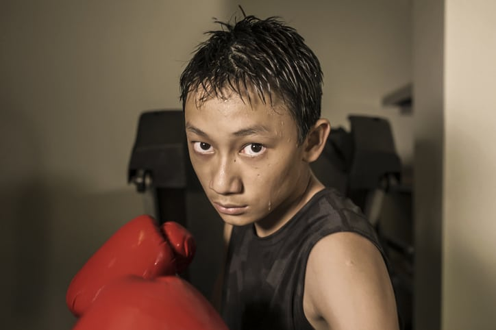 tough and cool young boy punching on heavy bag . 13 or 14 years old Asian teenager training Thai boxing workout looking defiant as a badass fighter practicing sport at fitness club